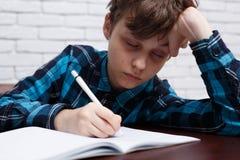 疲乏男小学生睡着,当学习在习字簿时 研究 免版税图库摄影
