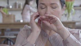 疲乏的不适的资深妇女画象有色的黑色头发藏品头的用手坐在的皮革沙发 股票录像