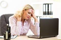 疲乏的中年女实业家在她的办公室 库存图片