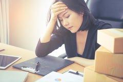 疲乏的亚裔办公室工作者用在她的顶头头疼的手 免版税库存图片
