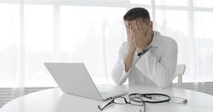 疲乏的人医生研究在诊所的一台膝上型计算机 股票视频