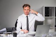 疲乏的人在显示枪标志的办公室 免版税库存照片