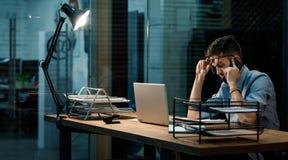 疲乏的人在有膝上型计算机的办公室 免版税库存图片