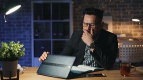 疲乏的人画象与膝上型计算机打呵欠的睡觉在计算机上一起使用在晚上 股票录像