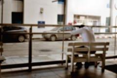 疲乏的人被弄脏的照片坐长凳 免版税库存图片