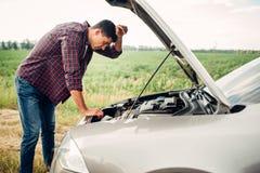 疲乏的人设法修理一辆残破的汽车 免版税库存照片