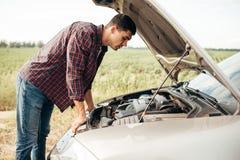 疲乏的人设法修理一辆残破的汽车 免版税库存图片