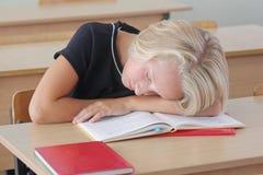 疲乏的儿童女小学生睡觉在教训期间在书桌在教室 免版税图库摄影