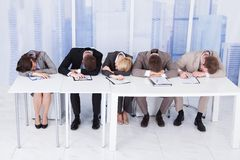 疲乏的公司人事干事在桌上 免版税库存图片