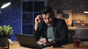 疲乏的办公室工作者画象使用膝上型计算机打呵欠的工作的在办公室在晚上 股票录像
