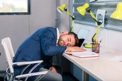 疲乏的办公室工作者睡着了在一台开放膝上型计算机的键盘 在办公室里面 免版税库存照片