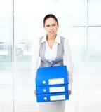 疲乏的劳累过度的女商人举行文件夹堆 库存图片