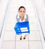 疲乏的劳累过度的女商人文件夹堆 免版税库存照片