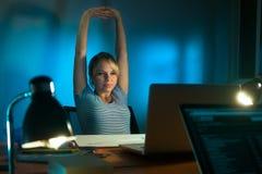 疲乏的后工作在个人计算机的妇女室内设计师在晚上 库存图片