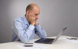 疲乏的商人与膝上型计算机一起使用 库存照片