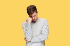 疲乏的商人或严肃的年轻人在黄色演播室背景激动头疼 库存图片