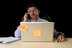 疲乏的商人遭受的工作压力在与便携式计算机的晚上后浪费了担心繁忙在办公室 库存图片