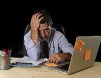 疲乏的商人遭受的工作压力在与便携式计算机的晚上后浪费了担心繁忙在办公室 库存照片