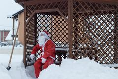 疲乏的圣诞老人坐木椅子在雪以后REM工作  图库摄影
