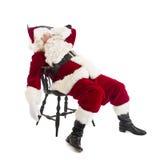 疲乏的圣诞老人坐椅子 图库摄影