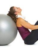 疲乏的坐在健身球附近的健身少妇 免版税库存照片