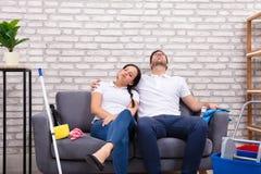 疲乏的夫妇坐沙发 免版税库存图片