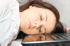 疲乏的女商人睡着了在膝上型计算机旁边 库存图片