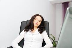 疲乏的女商人睡着了在膝上型计算机旁边 免版税库存图片