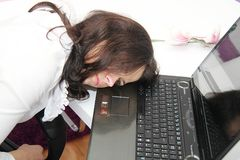 疲乏的女商人睡着了在膝上型计算机旁边 免版税库存照片