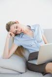 疲乏的女实业家小睡的坐她的长沙发 免版税图库摄影