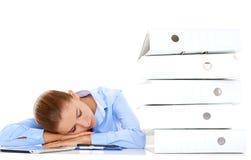 疲乏的女实业家睡着在她的书桌 免版税库存图片