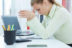 疲乏的女实业家降低了她的头和神色在桌上的纸 免版税库存图片