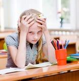 疲乏的女小学生在教室 查看照相机 库存图片
