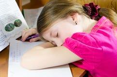疲乏的女小学生睡觉在书桌 库存照片