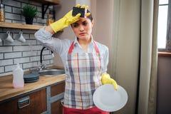 疲乏的女性擦净剂立场在前额的厨房和举行手上 她戴着围裙和黄色手套 白色妇女的举行 免版税库存图片