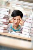 疲乏的妇女包围与书 免版税图库摄影