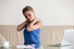 疲乏的妇女感觉脖子痛,惯座工作,不正确姿势 免版税库存图片