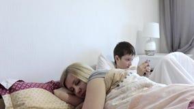 疲乏的妇女母亲醒在睡觉以后的和她的坐在床上和打流动比赛的太阳在小配件,智能手机 股票录像