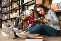 疲乏的学生在图书馆里坐地板阅读书 库存照片