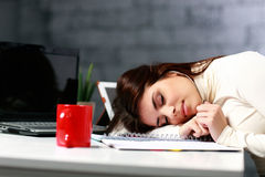 疲乏的学生睡着的在桌上 免版税库存图片