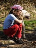 疲乏的小女孩拥抱她的狗 免版税库存照片