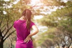 疲乏的年轻亚裔体育女孩感觉在她的后面和臀部的痛苦,当行使,医疗保健概念时 免版税库存照片