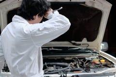 疲乏的年轻亚裔技工人画象制服的有有汽车的板钳的在修理车库背景的开放敞篷 库存照片