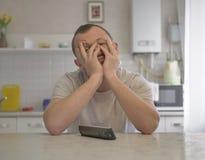 疲乏的年轻人坐厨房的背景 库存照片