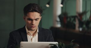 疲乏的年轻商人在咖啡馆工作的一张桌上坐膝上型计算机 自由职业者,通信,IT,疲乏 股票视频