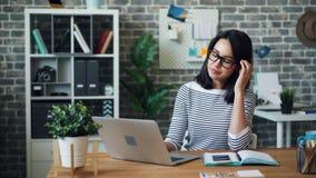 疲乏的年轻女人画象与膝上型计算机一起使用在然后打呵欠的办公室 影视素材