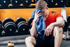 疲乏的年轻运动人在训练以后休假 健身、体育和生活方式概念 免版税图库摄影