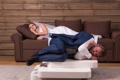 疲乏的新娘和新郎在长沙发睡觉 免版税库存照片