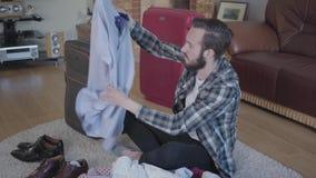 疲乏的有胡子的人坐地板和包装的手提箱 准备的概念旅途的 疏散的衣裳 股票录像
