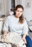 疲乏的母亲坐沙发,当她的洗涤在厨房的盘的daugrter 免版税库存照片